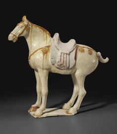 An amber and cream-glazed figure of a caparisoned horse, Tang dynasty (AD 618-907)