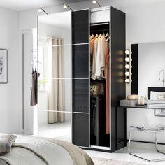 Chambre à coucher blanche avec combinaison armoire PAX foncée, mélange de bois foncé et de portes miroirs coulissantes.