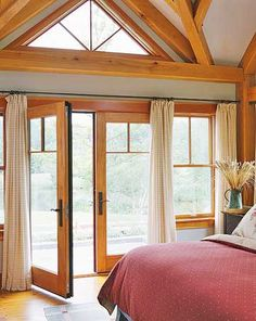 French doors from bedroom to patio are lovely. They match the wood in the windows and also the wood on the ceiling. Lots of unity and so many windows to provide a warm light. From Better Homes & Gardens.