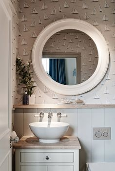 Wallpaper and circular mirror give this bathroom an inviting nautical look.