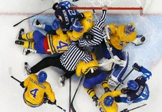 Officials attempt to separate players in the goal crease after a stoppage in play during a men's play-off semi-final ice hockey game (Sochi 2014 Olympics) Hockey Games, Ice Hockey, Olympic Sports, Semi Final, Face Off, World Of Sports, Winter Olympics, Separate, Goal