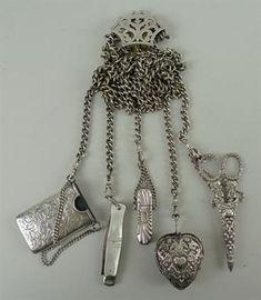 A Victorian silver five strand chatelaine, Birmingham 1898, holding scissors in a sheath, folding 'Ghurka' pocket knife, heart shaped pin cushion, aide memoire, and a pencil holder, 13.71toz.