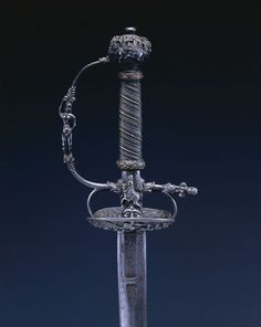 Small Sword Dated: 1650-1660 Culture: Netherlands Medium: steel, wood, copper wire; chiseled hilt; engraved blade Measurements: Overall - l:95.30cm (l:371/2 inches) Wt: .58kg; Blade - l:78.00cm (l:3011/16 inches); Grip - w:11.80cm (w:45/8 inches); Guard - l:8.30cm (l:31/4 inches) Source: © 2012 Cleveland Museum of Art