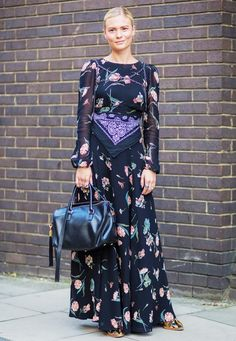 Pandora Sykes wears a floral maxi dress, chain harness, bandana around the waist, Saint Laurent leather duffle, and snakeskin boots