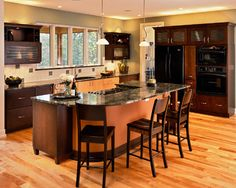 contemporary large center island with gas range top, dark granite, wood baseboards