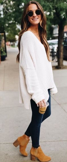 Oversized V neck knit sweater with blue jeans.