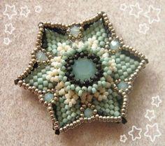 essai couleurs 1 - vedhæng i stjerneform med cabochon i lys turkise perler og hvide samt sølv seed - mørkgrå