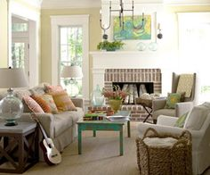 Love the pops of color on the coffee table, mantel art, and pillows