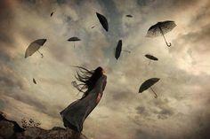 donna che osserva ombrelli che volano