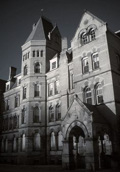 Riverside State Hospital. This insane asylum, as it was once called, sits hidden amidst green rolling hills, with a grand view of the mountainous landscape and a nearby river. The main building on the campus is a Kirkbride design in Gothic-revival style, where male and female patients were separated by the two wings on either side of a central administration section. Construction began in 1868, and finished in 1871
