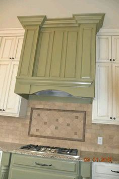 Kitchen Vent Hood - I like how they look to be part of the cabinetry,  but just in a different color.
