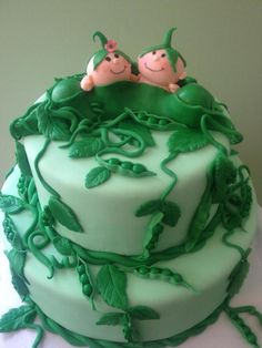 pea pod made from green fondant, containing two smiling baby figurines, and two peas, topping a light green two-layered cake, twin baby shower cakes, with pea shoots and dark green leaves