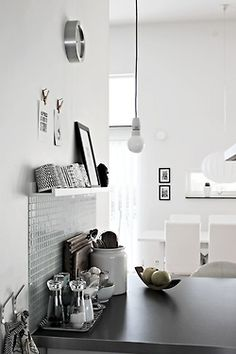 White and grey kitchen with exposed bulb light