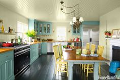 """""""It's a classic farmhouse kitchen, but the colors are idiosyncratic, personal, and much more vibrant than the standard white or gray,"""" McCabe says. A 19th-century American table is surrounded by Crate & Barrel Village chairs. Cabinets in Benjamin Moore's Stratton Blue. Walls in Green Ground, floor in Carriage Green, both by Farrow & Ball."""