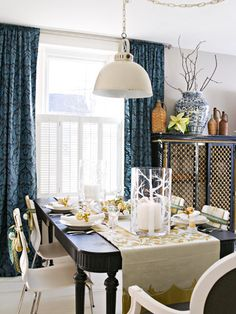 Traditional table, modern chairs, rustic pendant light, tone-on-tone drapes.  Navy, white, cream.