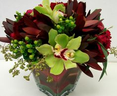 This is a cube vase floral arrangement that features cymbidium orchids and hypericum berries in a green color scheme with burgundy accents.  See our entire selection at www.starflor.com.  To purchase any of our floral selections, as gifts or décor, please call us at 800.520.8999 or visit our e-commerce portal at www.Starbrightnyc.com. This composition of flowers is generally available for same day delivery in New York City (NYC). SQ080
