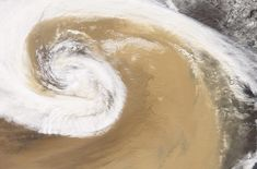 The Moderate Resolution Imaging Spectroradiometer (MODIS) on NASA's Terra satellite captured this image of a dust storm as it swirled over China in April of 2001. A strong temperate cyclone spun counter-clockwise over China, pushing a wall of dust as it moved. The deep tan dust is not only thick enough to completely hide much of the land surface below, but it almost forms its own topography, with ridges of dust rising up below the clouds. The spiral arms of white cloud are approximately…