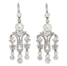 A pair of late Victorian pearl and diamond drop earrings, the earrings comprising a natural pearl surmount with two diamonds above, the pearl measuring approximately 6.5mm in diameter, surmounting a rose-cut and old-cut diamond-set fringe of floral and scroll design, the diamonds estimated to weigh a total of 2 carats for the pair, millegrain-set in silver with hook fittings, gross weight 10.4 grams, circa 1890