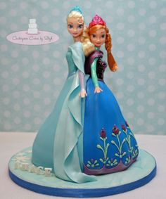 """Elsa and Anna double doll cake - I fell in love with the amazing Cup'N Cake design of Elsa and Anna cake a few months back right here on CC and when I was asked to re-create it I was so excited!! So here it is! The dolls are full size (barbie size) dolls which are wrapped in cling/syran wrap and standing up straight. The cakes are carved 8"""", 8"""", 6"""", 6"""" I carved Elsa's dress a bit more than Anna's, for Anna I added molding chocolate pleats to give it more body before I covered it with ..."""