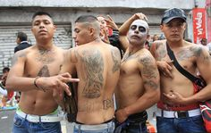 Santa muerte devotees showing off their tattoos during a procession