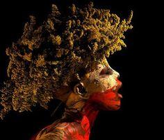 Mulher negra de perfil, sobre a cabeça, uma ramagem de plantas ressecadas e amareladas remetem a uma cabeleira black power. Pinceladas de tintas em amarelo e vermelho no rosto, pescoço e ombro. Da metade do rosto para cima, orelha e nuca destaca-se, o craquelado sobre a tinta amarela. Da metade do rosto para baixo, narinas, lábios, parte frontal do pescoço e colo, a tinta vermelha está sobreposta à pintura amarela.