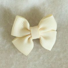 Sweet cream colored hair bow. It easily attaches with an alligator clip .Works best when hair band is in first.