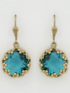 Vintage French earrings by La Vie Parisienne. Faceted teal crystal is encased in a filigree antique gold design