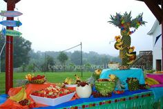 Fruit display with pineapple tree, fruit monkeys, pineapple parrots, banana dolphins, fruit bowls, and a palm tree fruit tray.