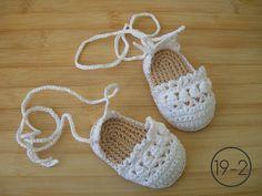 Alpargatas de blanco morado hechas a ganchillo con la suela imitando esparto, cordones largos para atar a los tobillos.