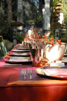 FOR LUNCH IN THE GARDEN AT DAWNRIDGE, DESIGNER HUTTON WILKINSON, TONY DUQUETTE INC., HAS SET THE TABLE WITH SFERRA LINENS, AND VENETIAN GLASS CORAL BRANCHES IN NAUTILUS SHELLS.