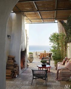 The stone terrace of designer and antiques dealer Richard Shapiro's Malibu beach house is furnished with rattan and wicker chairs and an early-20th-century octagonal table painted deep red. The large ceramic jar is 16th-century Thai.