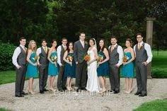 gray vests for groomsmen, gray suit for groom, bridesmaids in teal with orange chunky jewelery, and maids of honor in dark blue!