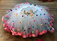 Cup Cake Tutu/ Sprinkle Tutu Cake/ Pom Pom Tutu Description: White tulle, pink and light blue satin ribbon with colorful pom poms *Please know there is a $10 charge for rush orders* Waistbands: made with 1-inch non-roll elastic, will stretch 2-3 inches to accommodate growth. Available