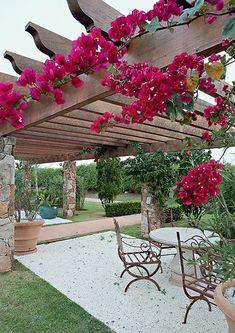 Para seguir o mesmo estilo provençal adotado no jardim, o paisagista abusou de materiais naturais na construção do pergolado cheio de flores