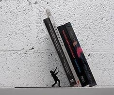 Sometimes the weight of knowledge contained in a book can crush a man, but sometimes just the weight of a book can literally crush a man as seen with this clever falling bookends that display a tiny man about to be obliterated by the falling books. $25