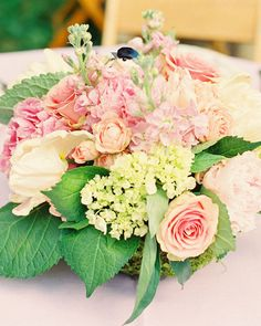 Peonies, garden roses, sweetpeas, lisianthus, and hydrangeas are displayed in…