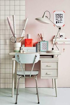 Pretty pink home office space with light blue and bright red accents with a white desk, white adjustable desk lamp and white floating shelves with pegs.
