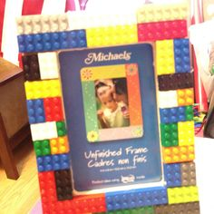 Unfinished wooden frame from Michael's then hot glue Legos around it.  Party then bedroom decoration.