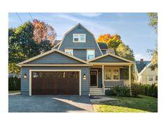 Beautiful exterior, love the half farmers porch and barn garage doors