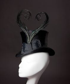 Black 'Viola' Top Hat-  This ladies hat is made from long-napped fur felt in gorgeous glossy black, polished to a high shine, and trimmed in black vintage ribbon, a large bow, and hand-curled feathers. These Ringneck Pheasant feathers are overdyed to match the trim, leaving the feathers' natural markings and iridescence still showing through. Fully lined in silk taffeta or shantung, so it looks as beautiful on the inside as it does on the outside.