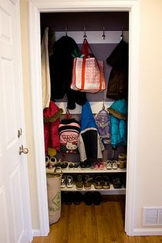 Entry closet organization system. Long hanging space on left side, from front to back wall.  The back wall has hooks and two rows of shoe storage along the bottom.