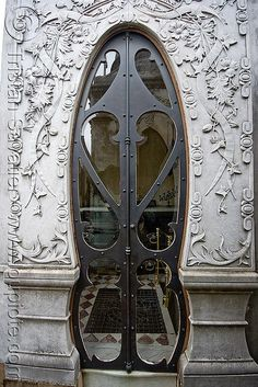 This doorway is art..wall carved design in relief...door arched metal and curved glass design...