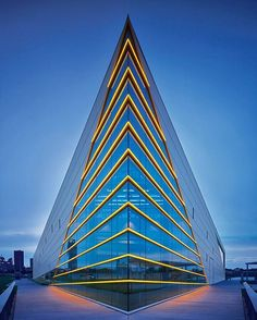 Golden accents gleam throughout Elliot + Associates' CHK Central Boathouse in Oklahoma City. Most dramatic are the golden yellow LEDs that run horizontally across the glass planes and form chevrons. Photography by Scott Mcdonald/Gray City Studios. #architecture #interiors #design #interiordesign #oklahoma #theater #facade