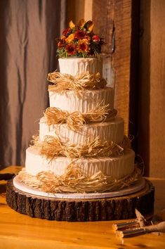 This four-tiered frosted caked was decorated with hay ribbon and adorned with a floral cake topper for the couple's Fall Connecticut barn wedding {Misty Enright Photography}