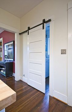 Lindy Williams Interiors - Laundry Room. Sliding barn door style entry to laundry room made from original craftsman wood door and industrial hardware