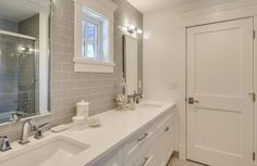 The guest bathroom is primarily white with his-and-hers sinks. The grey tile backsplash extends into the shower and tub enclosure.