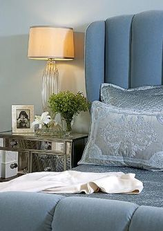 Bed, mirrored dresser as night table, glass lamp - warmed up with a golden shade, flower, greenery