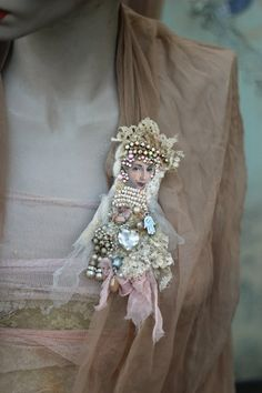 Vintage dolls, russian fairytales and iconic art inspired wearable art brooch. Unique mixed media brooch in shades of cream and ivory is made of nuno felted antique silk laces, soft tulle, composite clay, vintage ephemera, crystals, vintage pearls and seed beads. Mostly hand stitched details. Face is varnished with weather proof varnish. Brooch is backed with dusty blue leather and has secure brooch pin. About 14 cm high, 7 cm wide ( 2- 2,5 inch wide and 5,8 inch high ) Comes in a cardboard…
