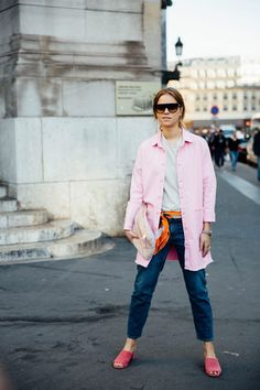 Pink jacket and mules, white top and jeans.