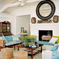 Pops of color in livingroom.  Round mirror over fireplace.  Blues, texture, mix of furniture styles.